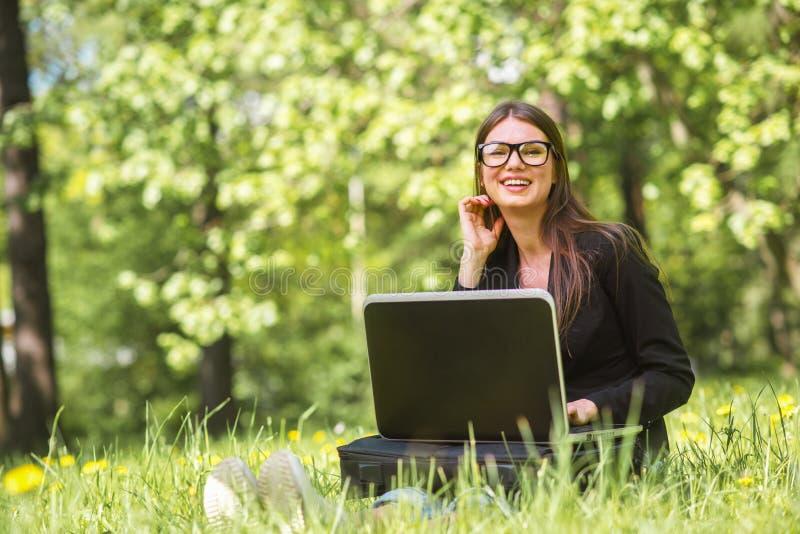 Επιχειρησιακή γυναίκα με το lap-top στο πάρκο στοκ εικόνες