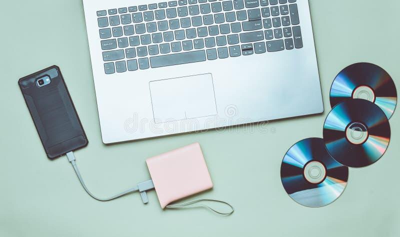Lap-top, smartphone, τράπεζα δύναμης, κινήσεις του CD, σε ένα πράσινο υπόβαθρο Ψηφιακά μέσα, συσκευές στοκ εικόνα