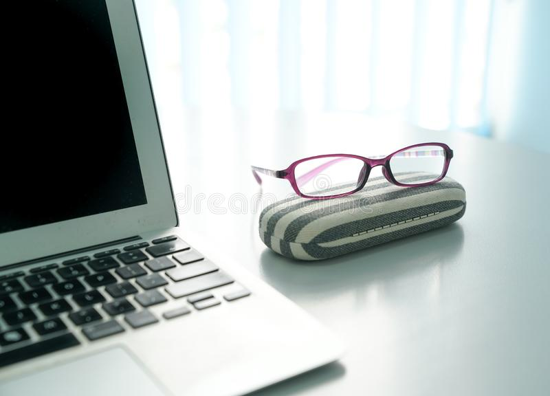 Lap top and reading glassess on office desk with windows at the back royalty free stock photography