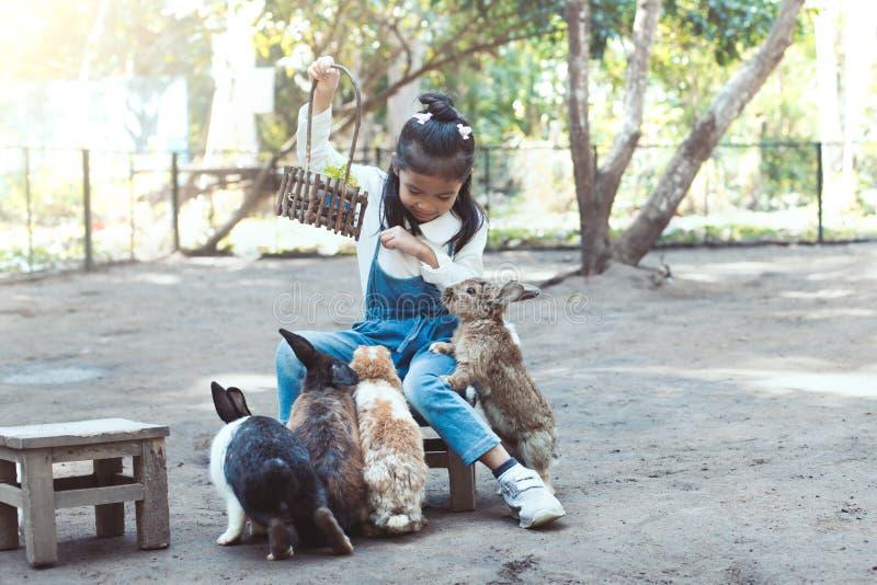 Lapin de alimentation de fille asiatique mignonne de petit enfant images stock