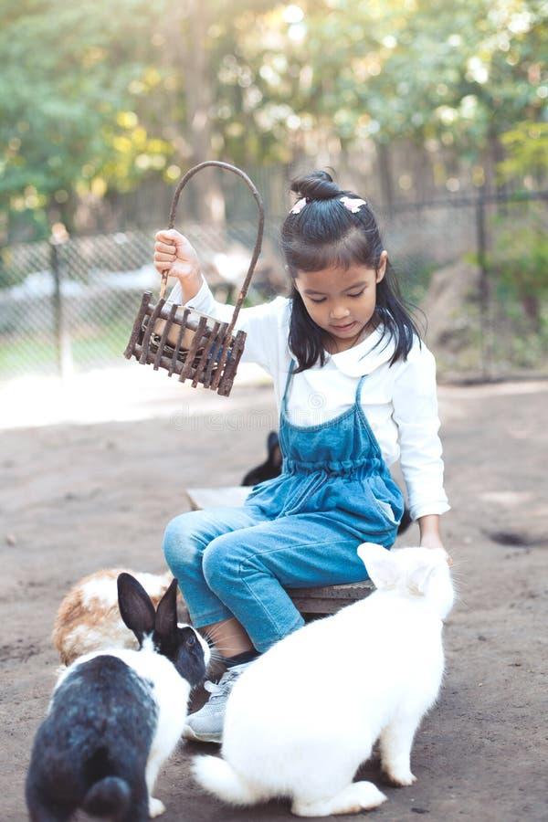 Lapin de alimentation de fille asiatique mignonne de petit enfant photos stock