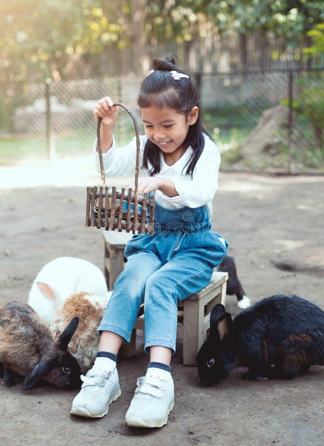 Lapin de alimentation de fille asiatique mignonne de petit enfant photo stock