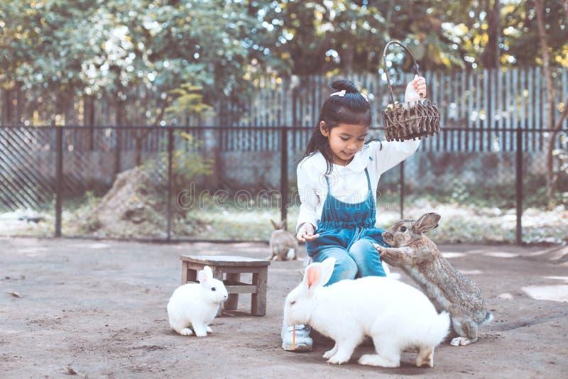 Lapin de alimentation de fille asiatique mignonne de petit enfant photo libre de droits