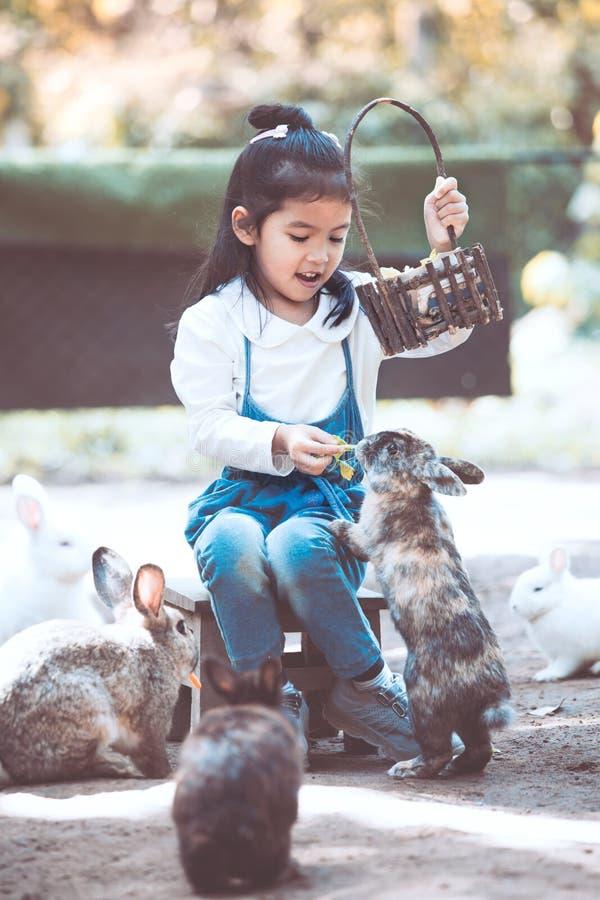 Lapin de alimentation de fille asiatique mignonne de petit enfant photographie stock libre de droits