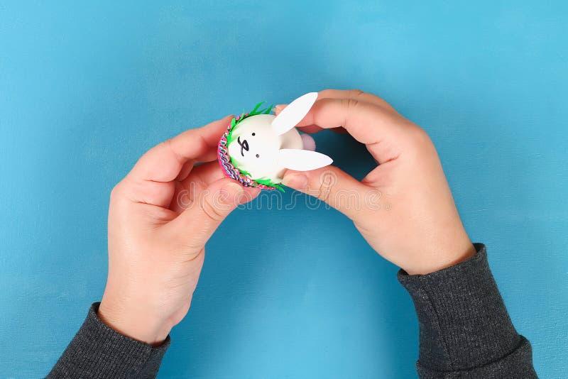 Lapin de Diy des oeufs de pâques sur le fond bleu Idées de cadeau, décor Pâques, ressort handmade images stock