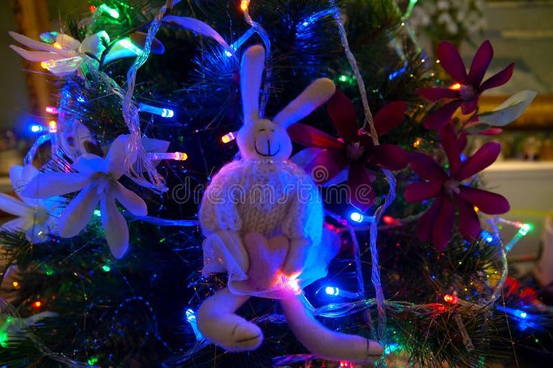 Lapin de Joyeux Noël se reposant sur un arbre de Noël décoré des fleurs et des lumières photos stock