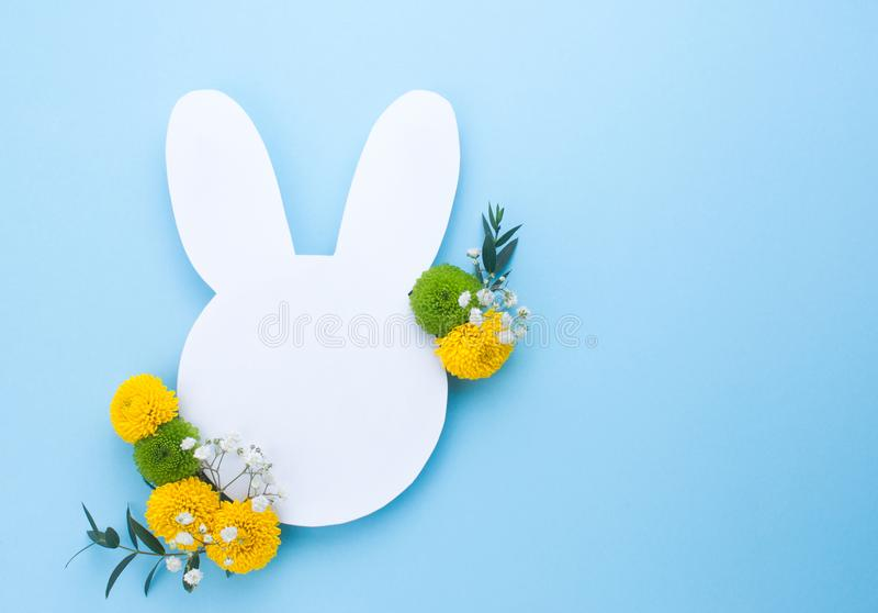 Lapin de Pâques avec des fleurs sur le fond bleu image libre de droits