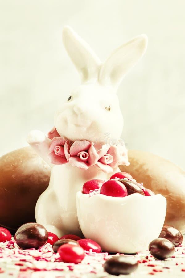 Lapin de Pâques de porcelaine avec les oeufs et le col de chocolat bruns et rouges photos stock