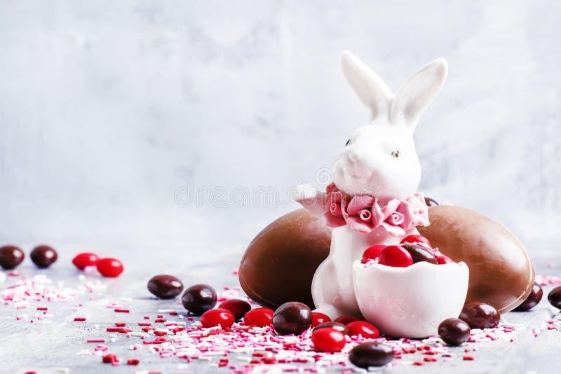 Lapin de Pâques de porcelaine avec les oeufs et le col de chocolat bruns et rouges photos libres de droits