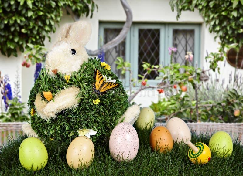 Lapin et oeufs de Pâques dans l'herbe verte avec la maison image stock