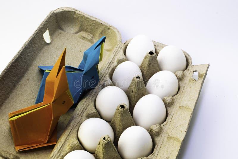 Lapins d'origami de papier coloré Lièvres de Pâques et oeufs blancs de poulet dans une boîte photos libres de droits