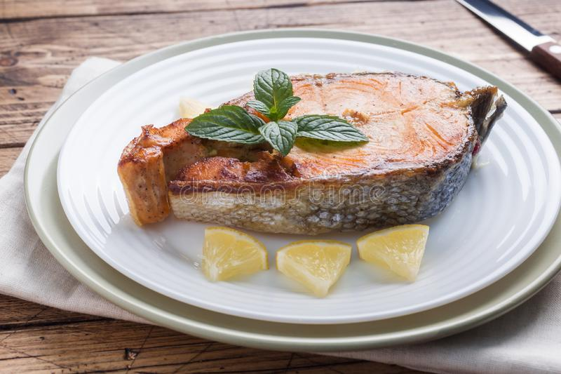 Lapje vlees gebakken vissenzalm op een plaat met citroen Houten lijst stock foto