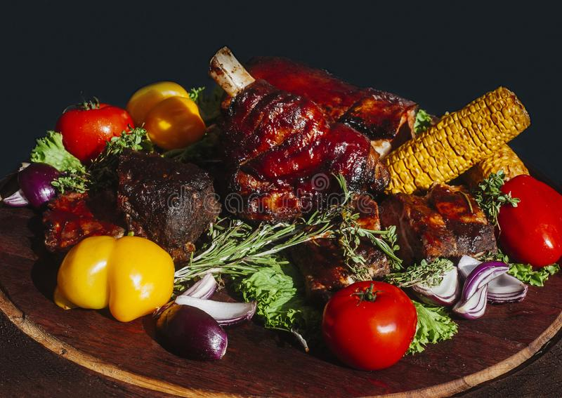Lapje vlees het dienen met geroosterde groenten op een zwarte om plaat  stock afbeeldingen