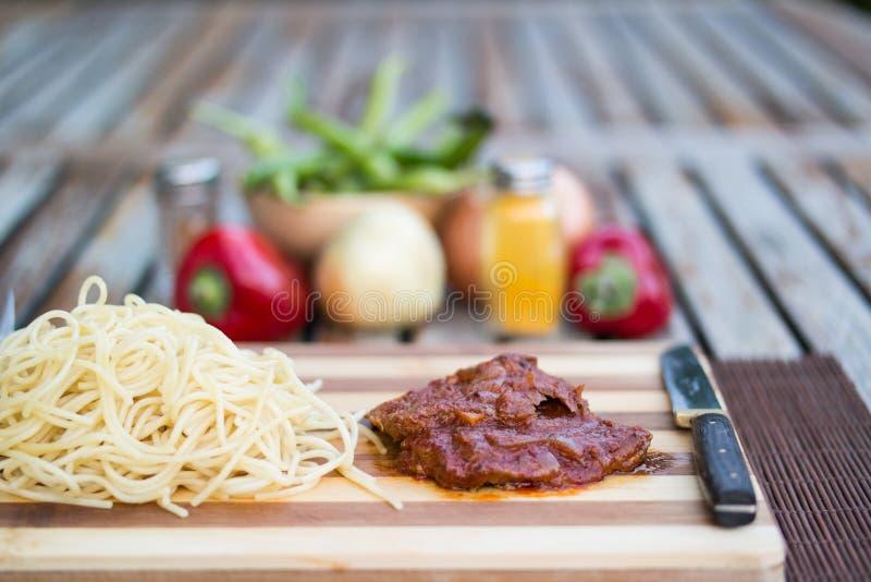 Lapje vlees met tomatensaus, sphagetti en groenten stock afbeeldingen