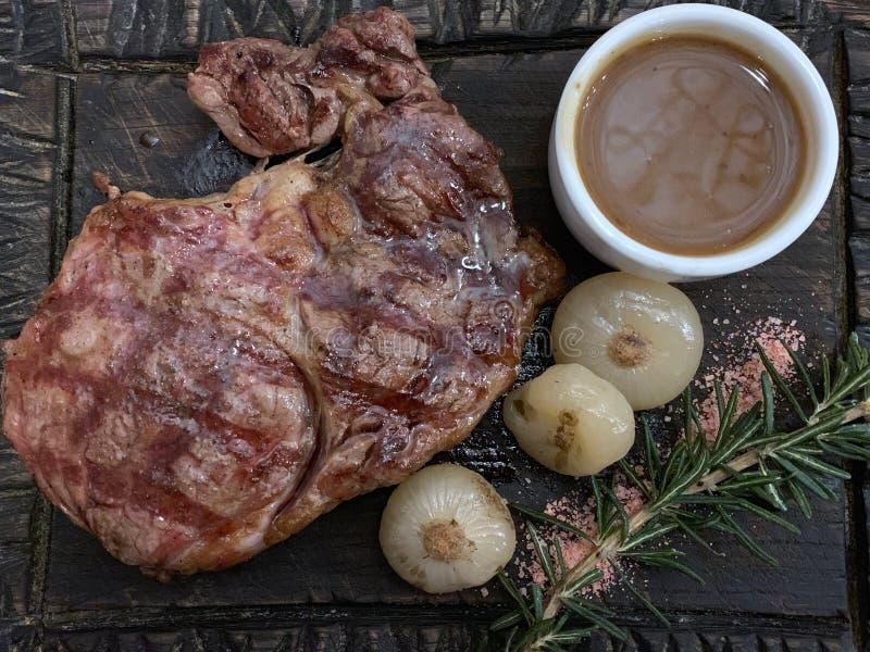 Lapje vlees met uien, rozemarijn en saus op een houten raad royalty-vrije stock afbeelding