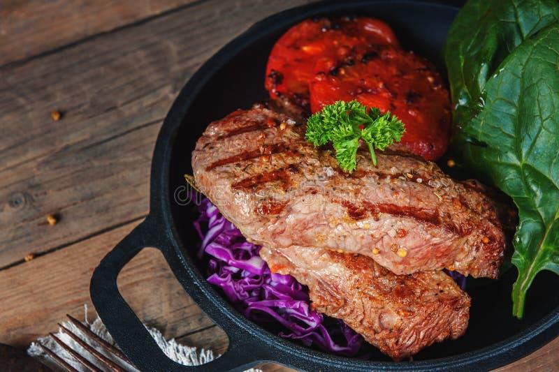 Lapje vlees zeldzaam met het bloed van groententomaten en spinazie in een pan op de houten lijst thuis worden geroosterd die Rust stock afbeeldingen