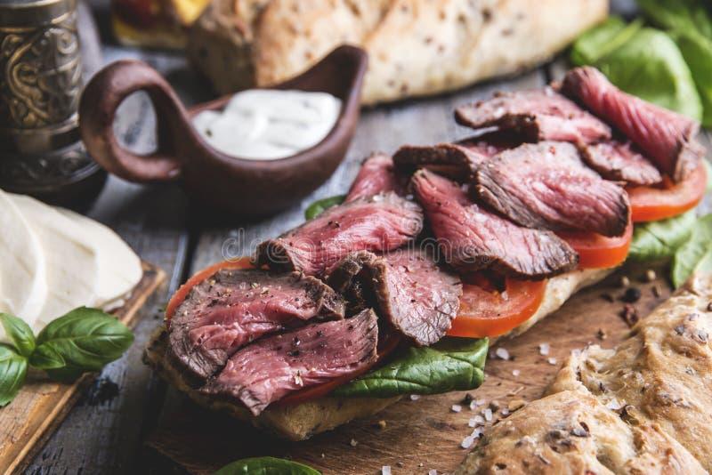 Lapje vleessandwich, gesneden braadstukrundvlees brood, mozarellakaas, spinaziebladeren, tomaat stock foto