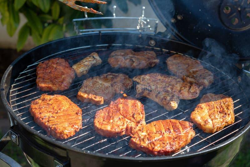 Lapjes vlees die over vlammende grill koken stock fotografie