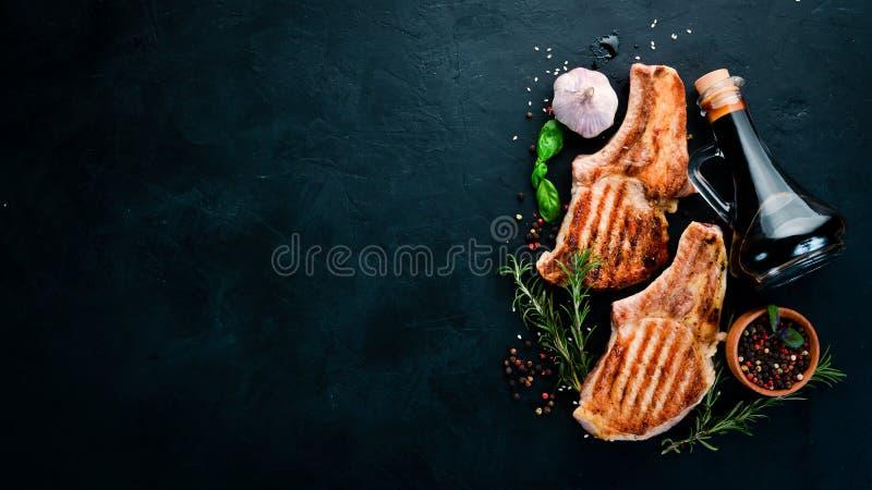 Lapjes vlees op het been met rozemarijn Grill, barbecue Op een zwarte steenachtergrond royalty-vrije stock fotografie