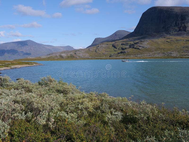 Lapland nature landscape with blue glacial lake Alesjaure with motor boat, birch tree forest, snow capped mountains. Northern. Sweden, at Kungsleden hiking stock photo