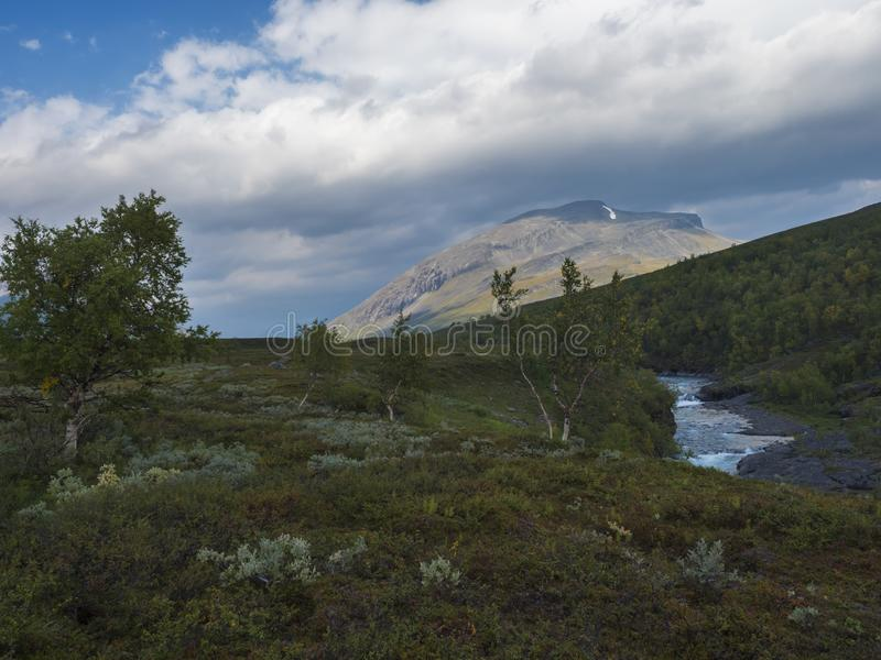 Lapland nature landscape with blue glacial river and Alesjaure STF Mountain cabin hut, birch tree forest, snow capped mountains. And lonely red tent, Northern stock images
