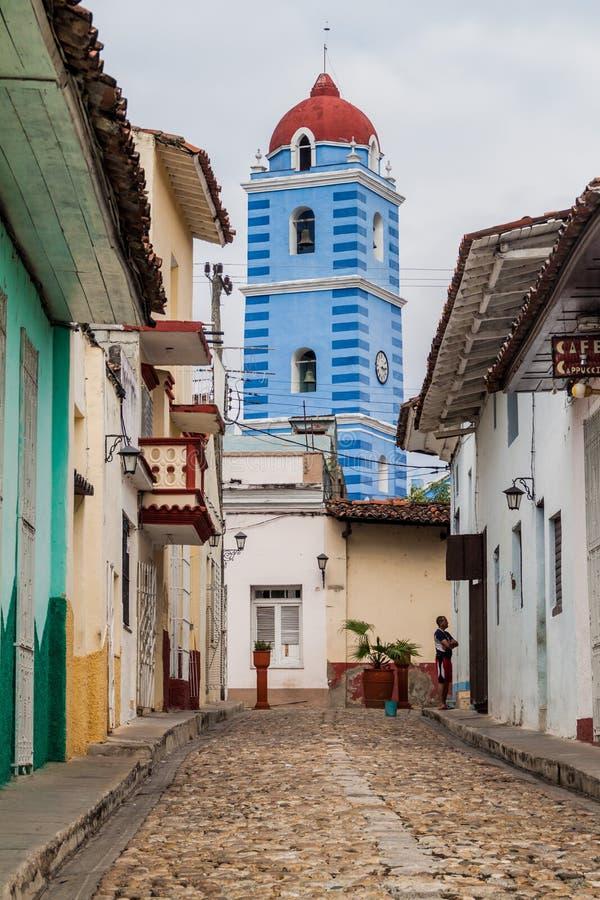 Lappad gata i Sancti Spiritus, Kuba Den Parroquial borgmästarekyrkan i backgrounen royaltyfri foto