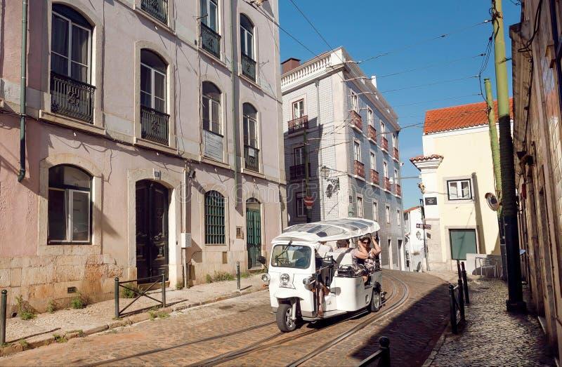 Lappad gata med den touristic automatiskrickshawen och lantliga hus av Alfama, historiskt centrum arkivfoton
