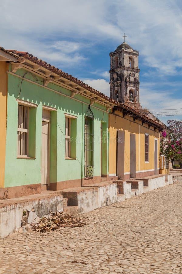 Lappad gata och färgrika hus i mitten av Trinidad, Kuba Fördärva av den Santa Ana kyrkan i backgrouen arkivbilder