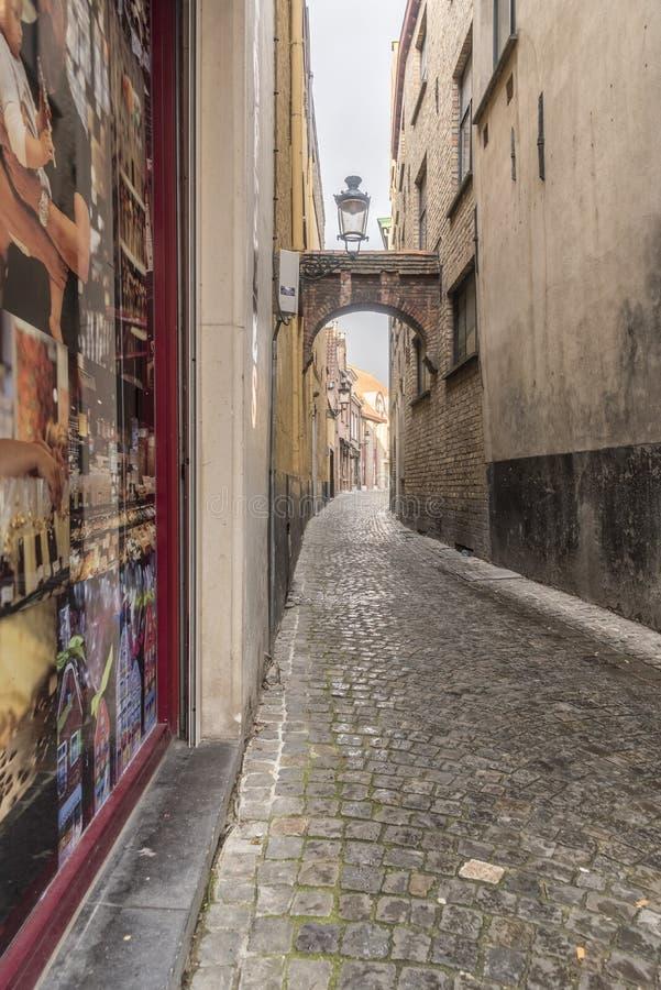 Lappad gränd för sidogata med bågen av Steenstraat Bruges royaltyfri foto