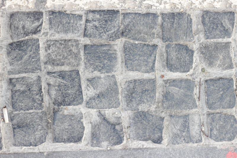 Lappad trottoar som göras av granitkuber arkivbilder