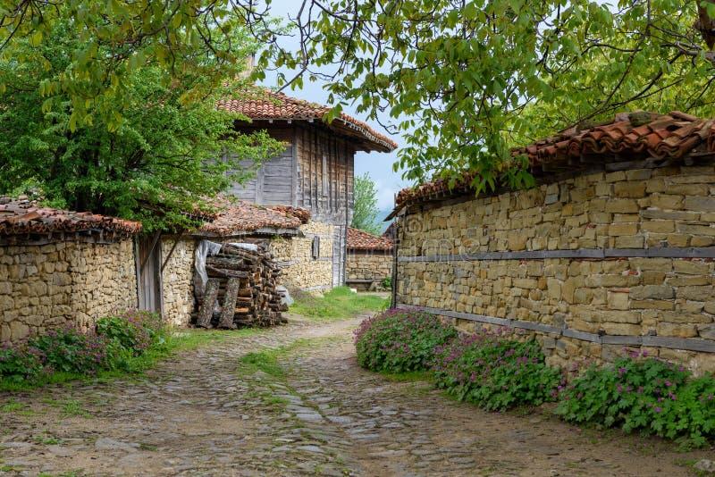 Lappad väg, gamla traditionella hus och valnötträdfilialer i Zheravna, Bulgarien arkivbild