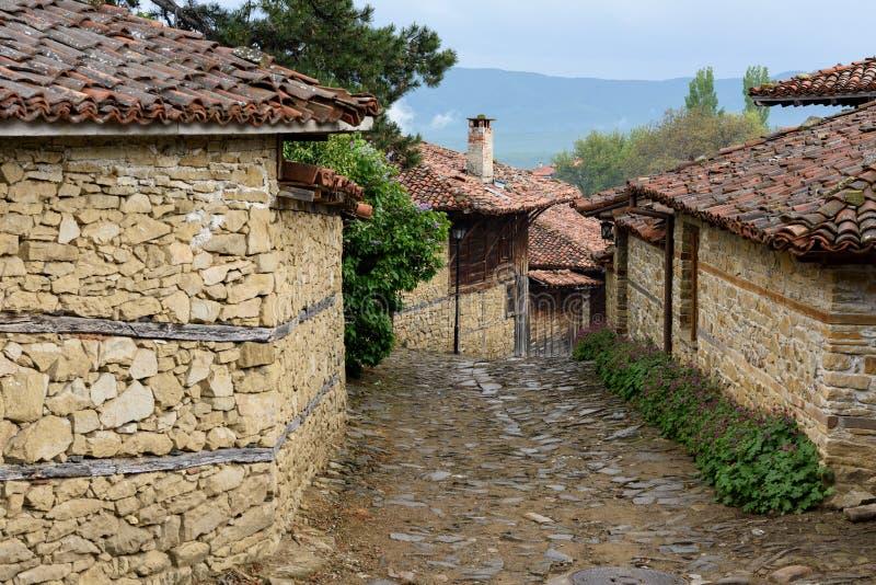 Lappad väg och gamla traditionella hus i Zheravna, Bulgarien royaltyfri bild