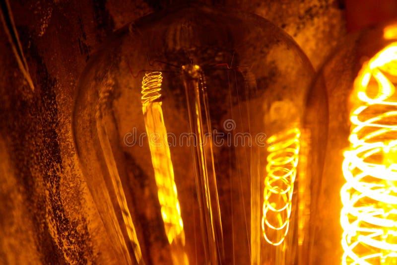 Lappade klassiska glödande Edison ljuskulor med synliga glödande trådar i natten royaltyfri bild