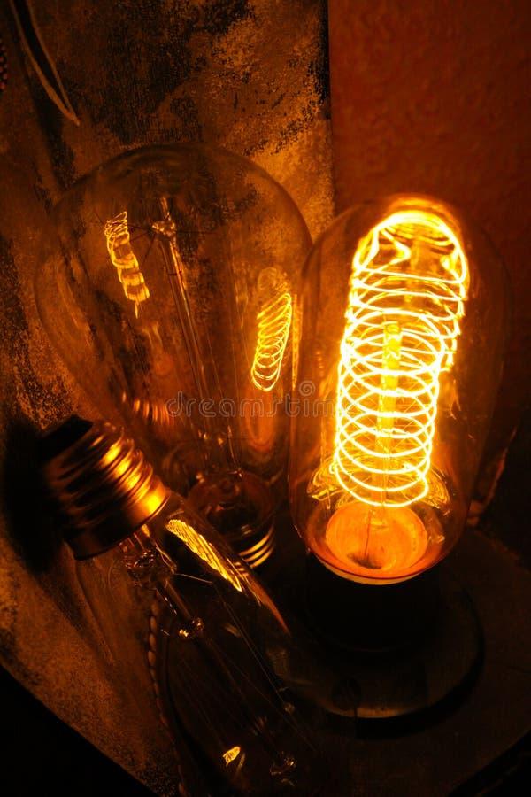 Lappade klassiska glödande Edison ljuskulor med synliga glödande trådar i natten arkivbild