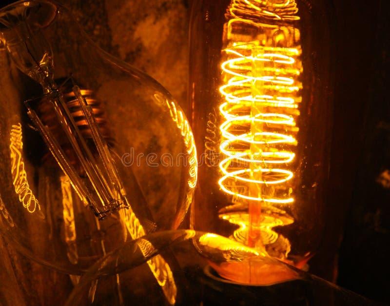 Lappade klassiska glödande Edison ljuskulor med synliga glödande trådar i natten fotografering för bildbyråer