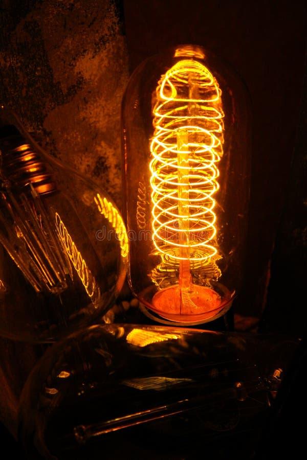 Lappade klassiska glödande Edison ljuskulor med synliga glödande trådar i natten arkivfoton