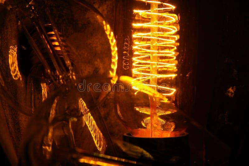Lappade klassiska glödande Edison ljuskulor med synliga glödande trådar i natten arkivbilder