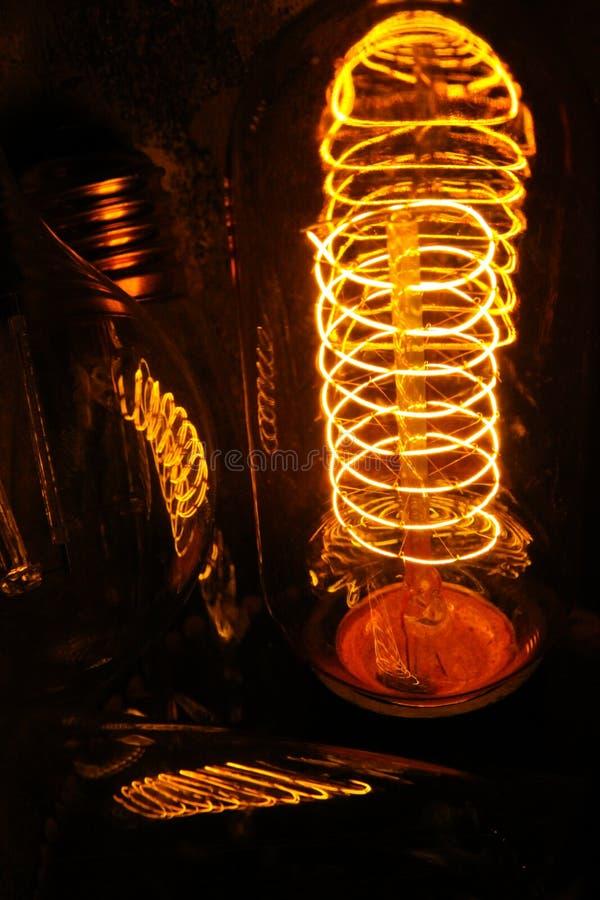 Lappade klassiska glödande Edison ljuskulor med synliga glödande trådar i natten royaltyfri fotografi