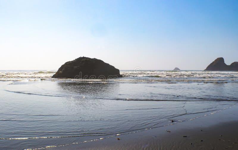 Lapping прилива на береге с огромными утесами выступающими из океана стоковые фотографии rf