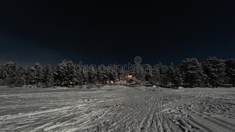 Lappish被月光照亮冬天风景,欢迎从旅馆的光在冻湖的边 库存图片