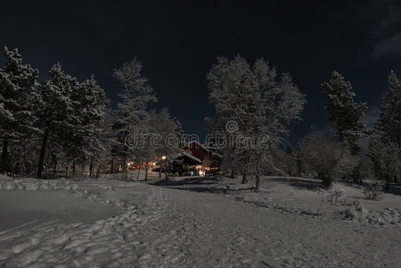 Lappish被月光照亮冬天风景,欢迎从旅馆的光在冻湖的边 免版税图库摄影