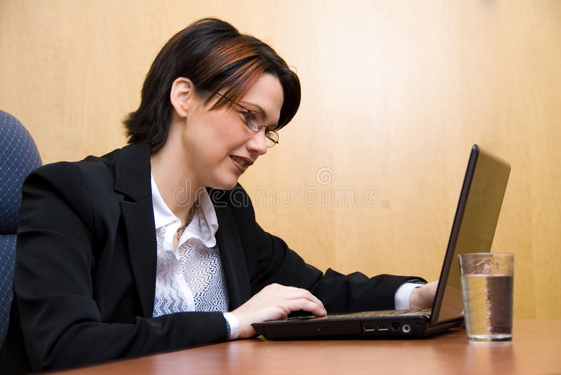 On the laptop. Business woman working her laptop royalty free stock images