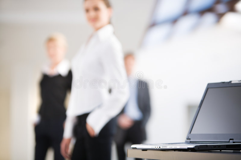 Laptop. Photo of black laptop on the background of business people