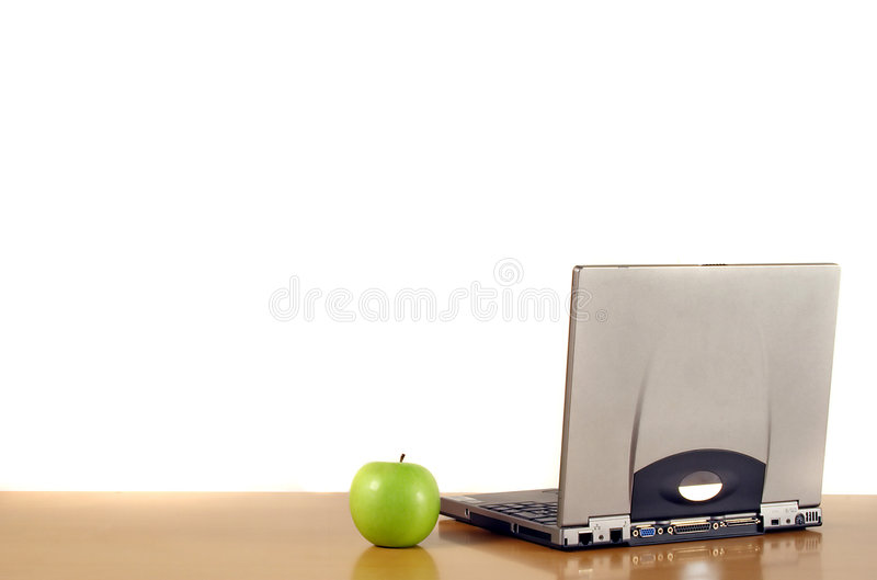 Laptop and apple on desk royalty free stock photo
