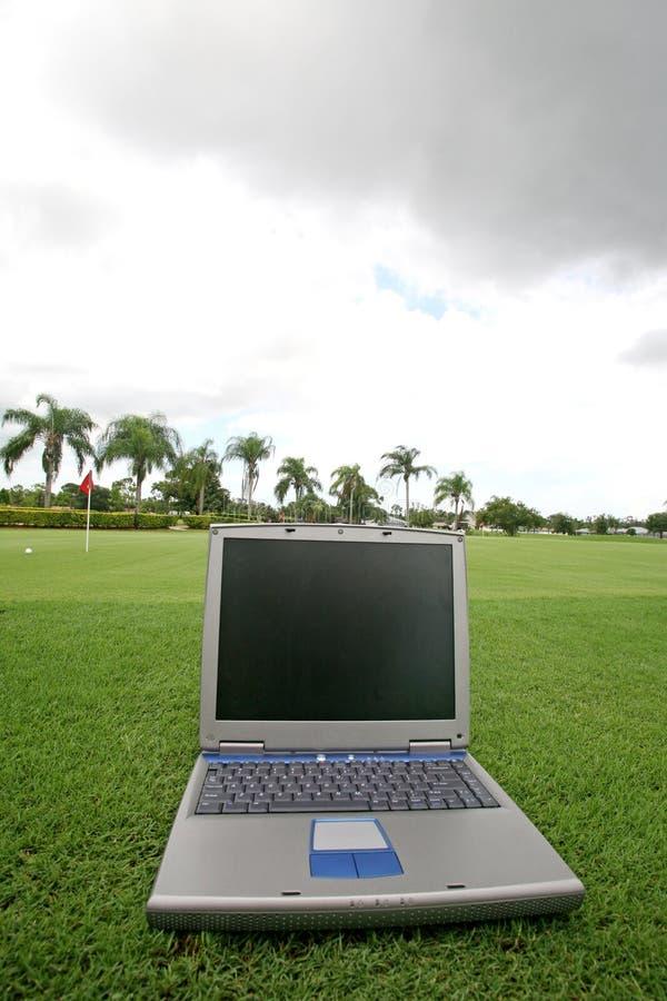 Laptop auf einem Golfplatz stockfotos
