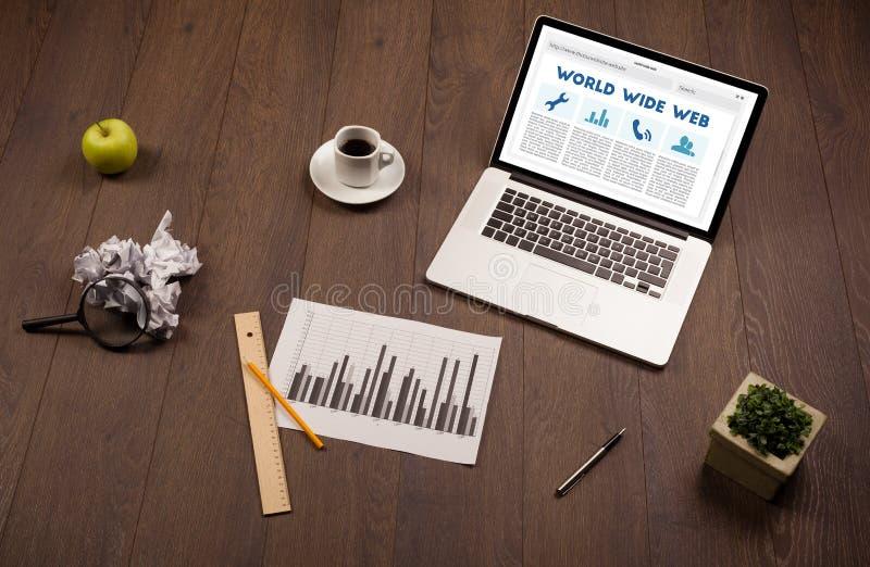 Laptop auf hölzernem Schreibtisch mit Büro suplies lizenzfreies stockfoto