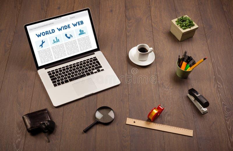 Laptop auf hölzernem Schreibtisch mit Büro suplies stockbild