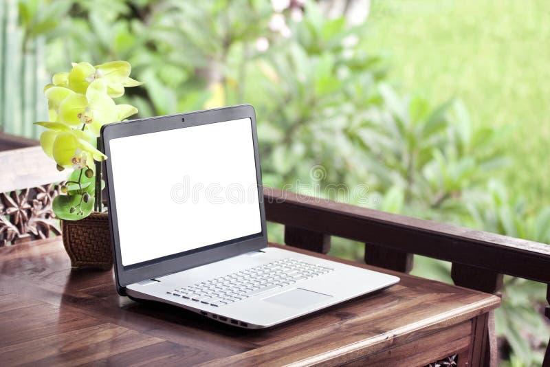 Laptop auf Holztischnatur stockfotos