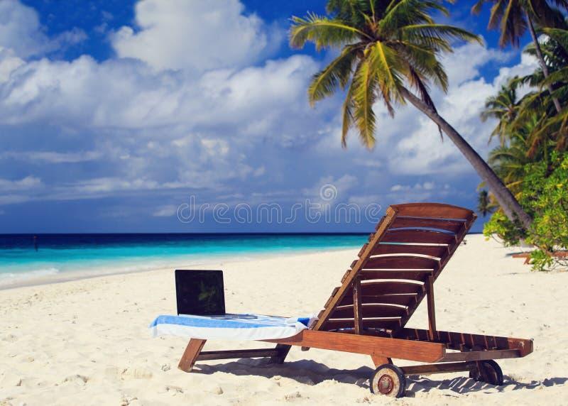 Laptop auf Stuhl in den tropischen Ferien lizenzfreie stockbilder