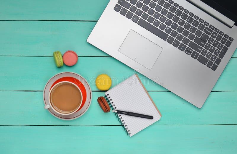Laptop, barwioni macaroons ciastka, filiżanka kawy, notatnik z piórem na błękitnym drewno stole Odgórny widok Mieszkanie nieatuto zdjęcie royalty free